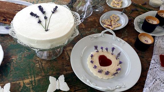 Gebäck und Torten aus Lavendel stehen auf einem Tisch.