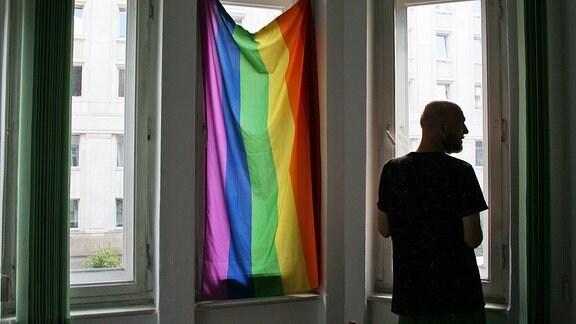 Ein Mann steht vor einem Fenster, in dem eine Regenbogenfahne hängt