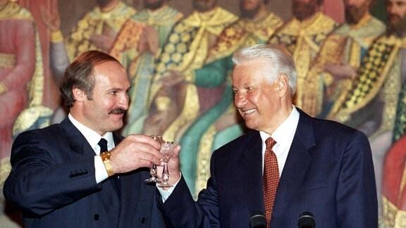 Zwei Männer in Anzügen stoßen gemeinsam mit Schnapsgläsern an. Es sind der ehemalige Präsident der Russischen Förderation, Boris Jelzin, und der Präsident von Weißrussland Alexander Lukaschenko.