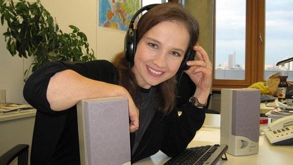 junge brünette Frau mit Kopfhörern stützt sich auf graue Lautsprecherboxen