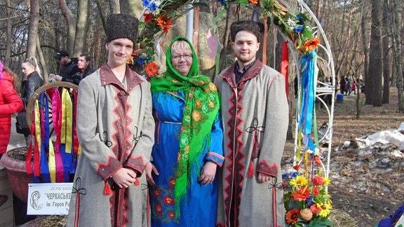 Zwei Männer und eine Frau in traditioneller ukrainischer Tracht.