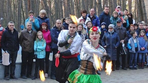 Mann und Frau in traditioneller ukrainischer Tracht jonglieren mit brennenden Stäben.