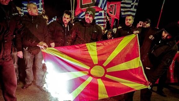 Im Bild zündet eine Gruppe von Männern die Fahne von Mazedonien.