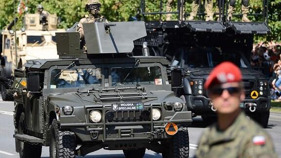 Polnischer Soldat vor gepanzerten Geländewagen.