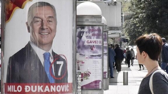 Eine Frau geht an einem Wahlkampfplakat von Milo Dukanovic, ehemaliger Staatspräsident von Montenegro, vorbei. Dukanovic kandidiert bei den Präsidentenwahle am 15.04.2018.