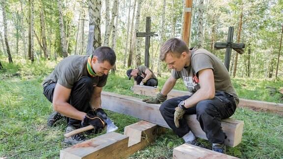 Junge Menschen sägen in einem Wald Holzkreuze aus Bäumen.