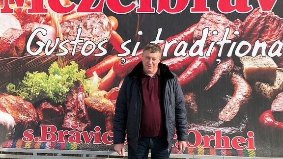 Ein Mann steht vor einer Reklametafel.