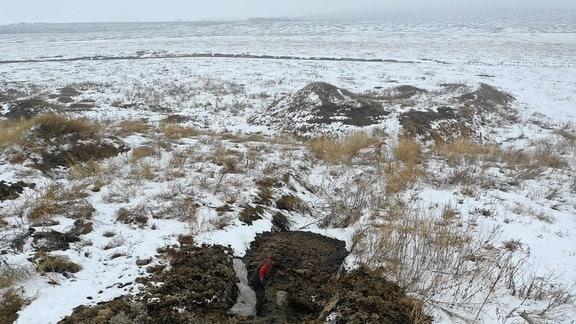 Verschneite, weite, Steppenähnliche Landschaft, in welcher ein Erdloch ausgehoben wird.