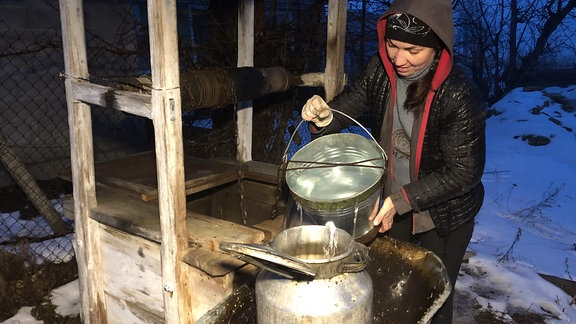 Eine Frau gießt aus einem Eimer Wasser in einen Blechkübel.