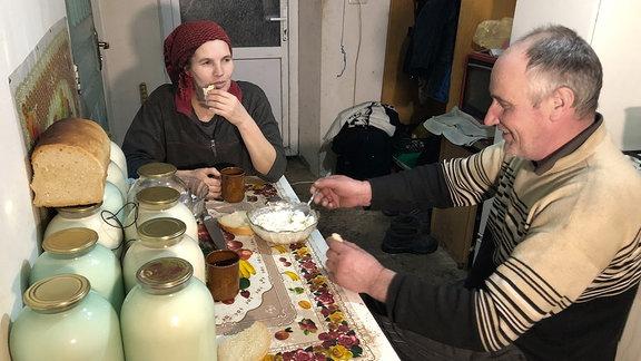Eine Frau und ein Mann sitzen an einem Tisch beim Abendbrot.