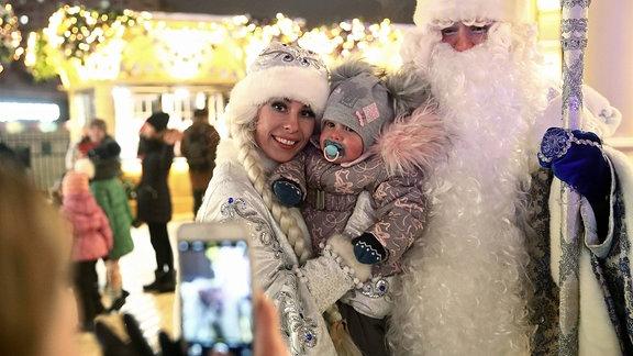 Eine als Väterchen Frost und Schneeflöckchen verkleidete Familie mit Kleinkind lässt sich mit einem Handy fotografieren.