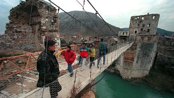 Ein bosnischer Soldat beobachtet, wie Kinder die von der EU errichtete Pontonbrücke in Mostar überqueren.