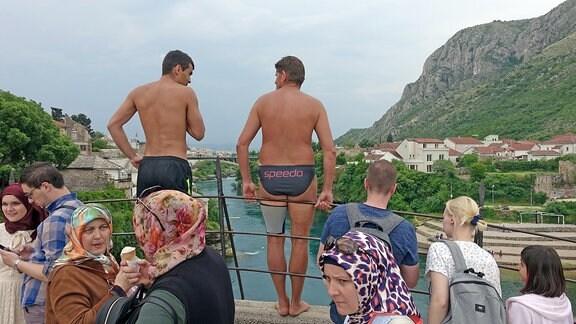 Zwei Männer in Badehose lehnen an einem Geländer auf der alten Brücke in Mostar, Bosnien.