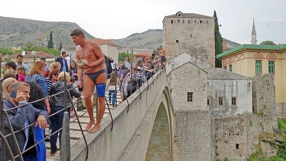 Ein Mann in Badehose sammelt von Touristen Geld ein auf der alten Brücke in Mostar, Bosnien.