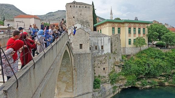 Mann in Neoprenanzug springt unter den Augen von Touristen von der alten Brücke in Mostar, Bosnien.