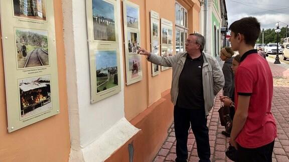 Menschen betrachten Fotos an einer Hauswand