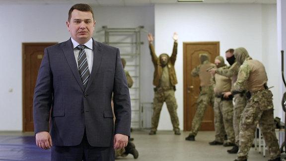 Mann im Anzug vor Gruppe vermummter Beamten mit Waffen.