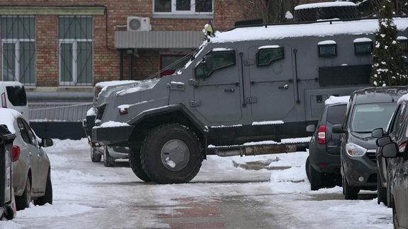 Gepanzertes Fahrzeug zwischen zivilen PKW im Schnee.