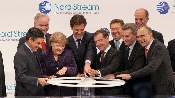 Mehrere Leute, darunter Bundeskanzlerin Merkel und Russlands Preier Medwdew, stehen vor einem großen Ventil mit Drehrad.