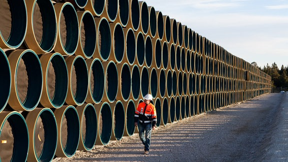 Mann läuft an riesigen, übereinander gestapelten Rohren entlang
