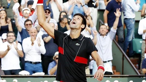 Tennisspieler Novak Djokovic reißt Hand nach oben. Publikum applaudiert im Hintergrund.