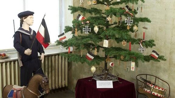 Ein Tannenbaum mit Schmuck aus der Kaiserzeit in Form von Reichsfahnen und Eisernen Kreuzen