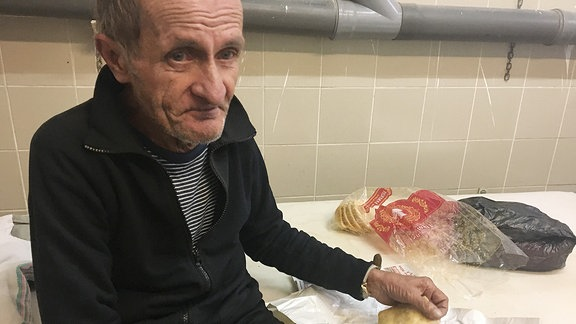 Ältere Mann schneidet mit einem Taschenmesser Speck von einem Stück ab
