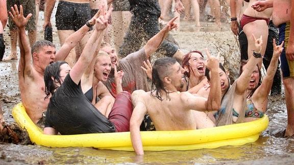 Festivalbesucher sitzen 2011 in einem Plantschbecken im Schlamm