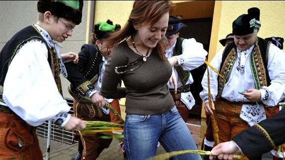 Eine Frau wird von Männern in Trachten ausgepeitscht.