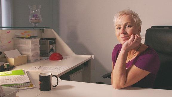 Eine Frau sitzt an einem Schreibtisch