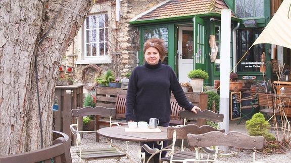 Eine Frau steht an einem runden Tisch