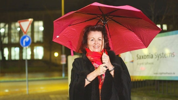 Eine Frau mit rotem Regenschirm