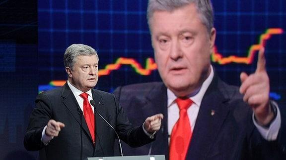 Ein Mann im Anzug steht an einem Rednerpult in einer Talk Show. Hinter ihm ist ein Monitor, der ihn überlebensgroß zeigt.