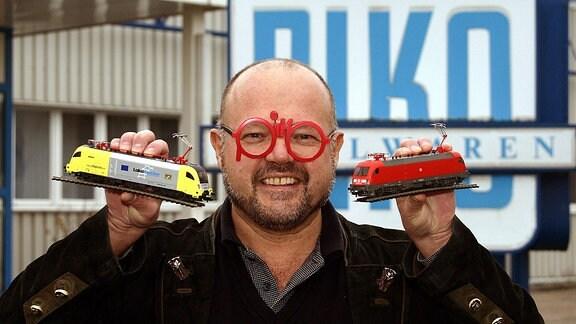 PIKO Chef Dr. Rene F. Wilfer, mit seiner markanten piko-Brille, posiert mit zwei Modell-Triebwagen seiner Firma.
