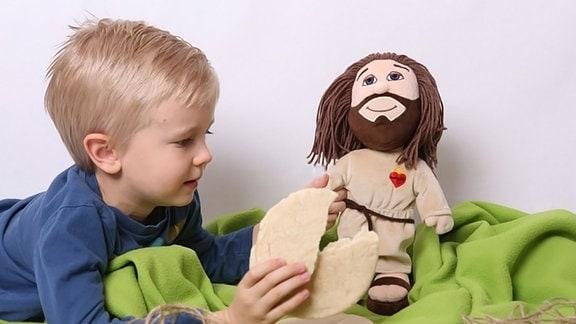 Kind mit Plüsch-Jesus