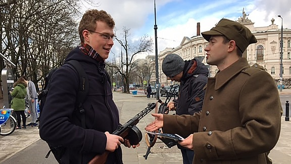 Studenten klären in Warschau Passanten über Partisanen auf.