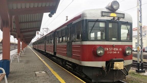 Ein Zug steht auf einem Bahngleis.
