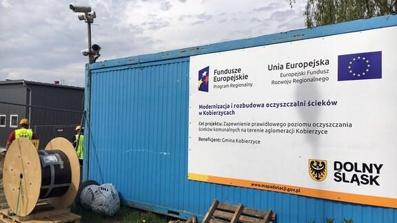 An einem Container hängt ein Schild