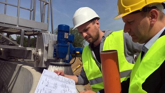 Bauarbeiter betrachten einen Bauplan
