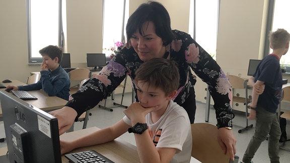 Lehrerin mit Schüler am Computer