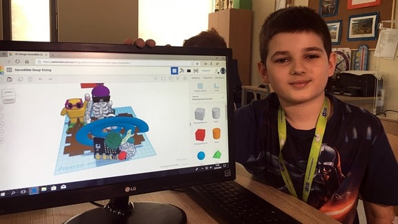 Junge neben Computermonitor