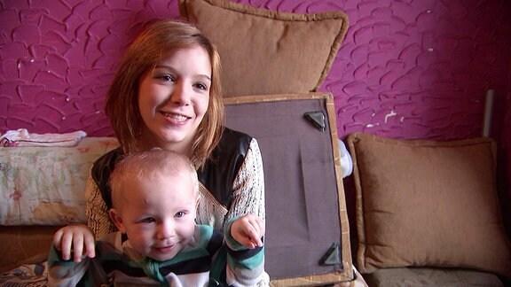 Ein Kleinkind und eine junge Frau sitzen auf einem Sofa.