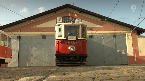 Rote Straßenbahn fährt aus Depot
