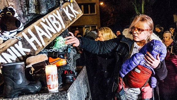 Frau mit Kind nimmt an einer Demonstration teil.