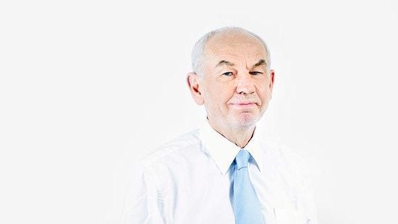 Älterer Mann mit schütterem grauem Haar in weißenm Hemd mit blauer Krawatte