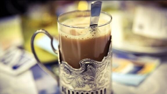 Kaffee mit Milch in einem Glas mit stilvoller Metalleinfassung