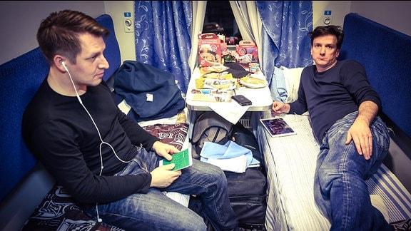 Zwei junge Männer in einem Zugabteil
