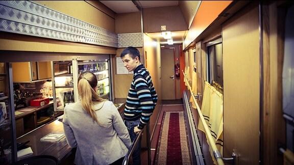 Zwei junge Leute im Speisewagen eines Zuges