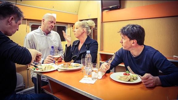 Passagiere beim Essen im Speisewagen eines Zuges