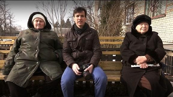 Ein Mann sitzt zwischen zwei Frauen